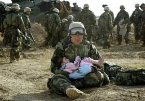 U.S. Marine holds Iraqi child after crossfire ripped apart family in central Iraq